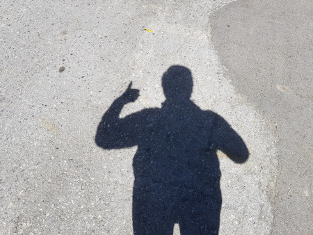businessman's shadow raising hand show thumb up symbol on cement floor. business success concept.の写真素材