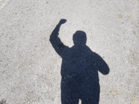 Men's shadow raising hand on cement floor because of win or success business.の写真素材