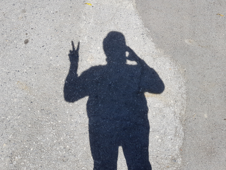 businessman's shadow raising hand show thumb up symbol on cement floorの写真素材