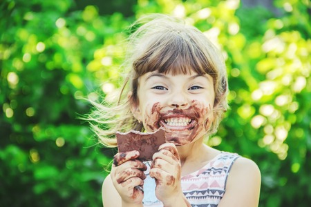 Foto de A sweet-toothed child eats chocolate. Selective focus. nature. - Imagen libre de derechos