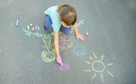 Child draws a family on the pavement with chalk. Selective focus. nature.
