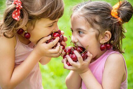 Photo pour Children eat cherries in the summer. Selective focus. - image libre de droit