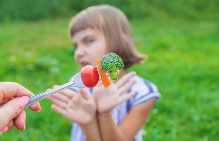 Photo pour child eats vegetables broccoli and carrots. Selective focus. - image libre de droit
