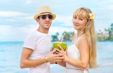 Photo pour A man and a girl on the beach are drinking coconut. Selective focus. - image libre de droit