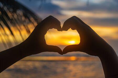 Photo pour Girl makes heart hands at sunset. Sri Lanka. Selective focus. nature. - image libre de droit