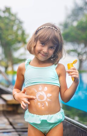Photo pour Child on the beach with sunscreen on his back. Selective focus. - image libre de droit