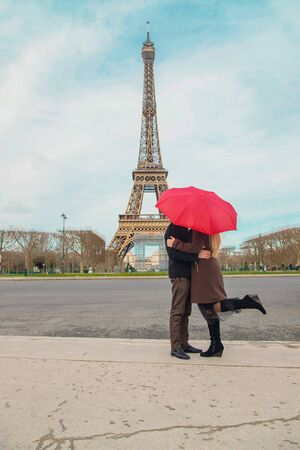 Photo for Lovers with a red umbrella near the Eiffel Tower in Paris. Selective focus. nature. - Royalty Free Image