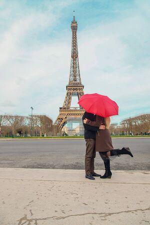 Foto de Lovers with a red umbrella near the Eiffel Tower in Paris. Selective focus. nature. - Imagen libre de derechos