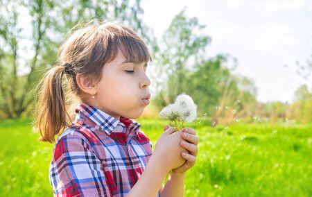 Photo pour Child girl with dandelions in the park. Selective focus. - image libre de droit