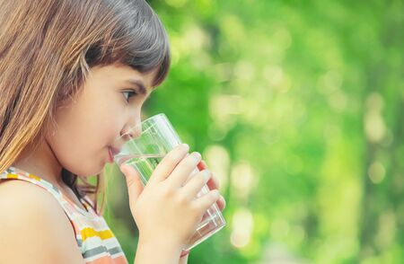 Photo for A child drinks water from a glass on the nature. Selective focus. Drink. - Royalty Free Image