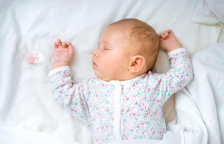 Photo pour Newborn baby sleeps on a white bed. Selective focus. People. - image libre de droit