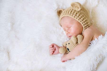 Photo pour A newborn baby sleeps with a teddy bear. Selective focus. people. - image libre de droit