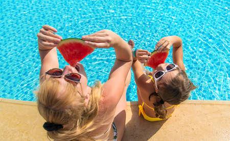 Photo pour Mother and child eat watermelon near the pool. Selective focus. Food. - image libre de droit