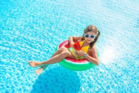 Photo pour Child girl eats watermelon near the pool. Selective focus. Kid. - image libre de droit
