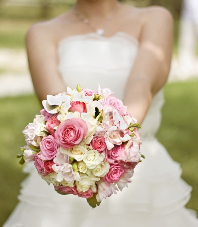Bride in a white dress with a wedding bouquet of white and pink flowers