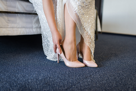 The bride touches her beige wedding shoes. The bride is wearing her wedding shoes. Wedding day.の写真素材