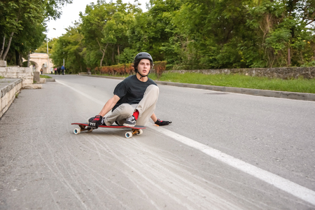 A young guy action makes a slide on a longboard in the resort area of the city