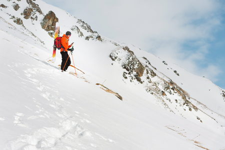 a ski freerider standing on a slope into a deep snow powder photographs the landscape on his mobile phone
