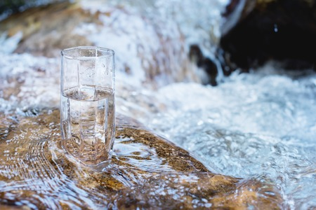 Photo for A glass glass with pure mountain drinking water stands on a rock in the course of a mountain river against the backdrop of seething cascades and waterfalls of a mountain river. The concept of pure mineral drinking water. Eco-friendly products healthy concept . - Royalty Free Image