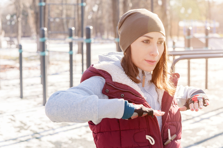 Foto de Sports girl in warm clothes on a sunny day does a warm-up on the outdoor sports field in the winter in spring or autumn during the cold season on the background of bars and horizontal bars - Imagen libre de derechos