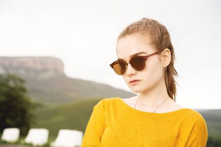 Photo for Portrait of a young attractive serious girl in sunglasses against the background of rocks and sky. Seriousness in the millenial generation - Royalty Free Image