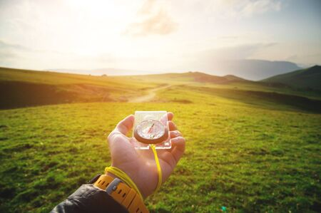 Foto de Male hand with a magnetic compass ea against the backdrop of a beautiful landscape at sunset. The concept of navigating the search for your own path and orientation to the cardinal points - Imagen libre de derechos