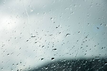 Photo pour Natural background Drops on both sides of the glass from the rain and from the fogging abstract view, raindrops against the blue glass and the blurred landscape of the gradient of blue and green - image libre de droit