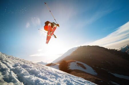 Photo for man skier in flight after jumping from a kicker in the spring against the backdrop of mountains and blue sky. Close-up wide angle. The concept of closing the ski season and skiing in spring - Royalty Free Image