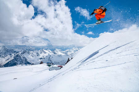 Photo pour A male skier in an orange suit flies in the air after jumping from a snow sweep high in the Caucasian mountains on a sunny day amid snow-capped mountains of blue sky and white clouds - image libre de droit