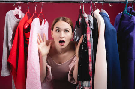 Photo pour Surprised young woman in stupor and confusion chooses between different clothes with a sad face - image libre de droit