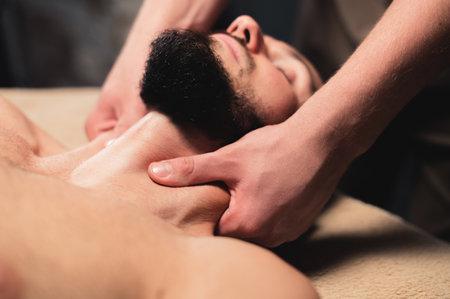 Foto de Close-up Professional neck massage to a bearded male athlete in a dark room of a spa massage room - Imagen libre de derechos