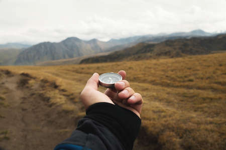 Photo for First-person view of a male traveler s hand holding a magnetic compass against the backdrop of a mountainous area. Orientation and finding your way - Royalty Free Image