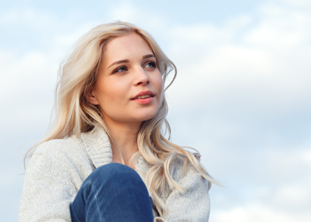 Photo for Beautiful happy blonde in a gray sweater and jeans smiling against the blue sky. Travel, leisure, tourism concept. - Royalty Free Image