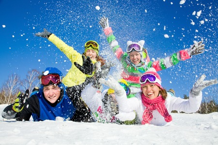 Group of teens playing on snow in ski resort