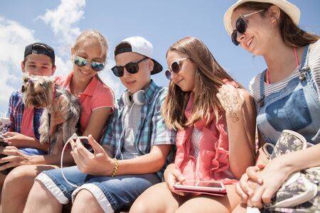 Photo for group of teenagers spending time together with gadgets - Royalty Free Image