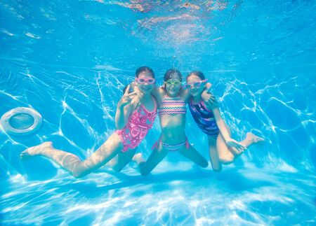 Photo pour group of little girls swimming  in pool  underwater. - image libre de droit