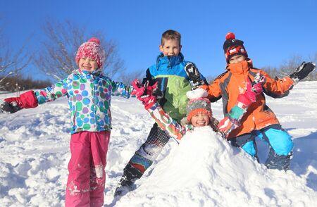 Foto de Group of children playing on snow in winter time - Imagen libre de derechos