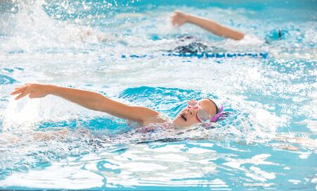 Photo pour little girl swimming in the pool at the training in swimming - image libre de droit