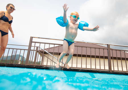 Photo for young mother with little son jumping to swimming pool - Royalty Free Image