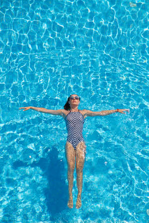 Photo pour Young woman relaxing in the swimming pool - image libre de droit