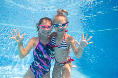 Photo pour Two little girls swimming in pool. under water photo, - image libre de droit