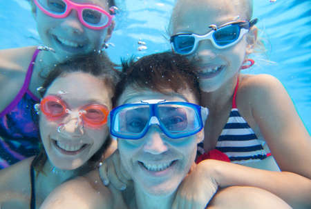 Photo for underwater photo of little boy with his family swimming in pool - Royalty Free Image