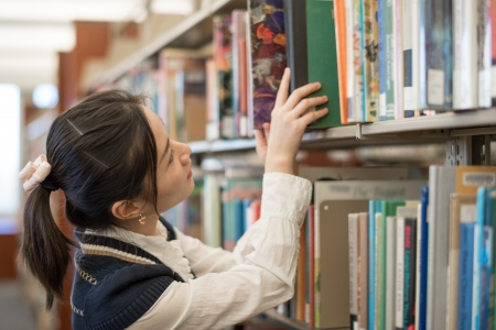 Young female student putting a green book back onto a bookshelf in library
