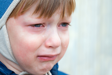 little boy was crying from hurt, tears stream down cheeks. emotion child sadness. kid cry