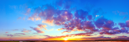 beautiful landscape panorama with blue sky, clouds and sunset. panoramic view of sunrise, a new day. sun rays shine through  clouds