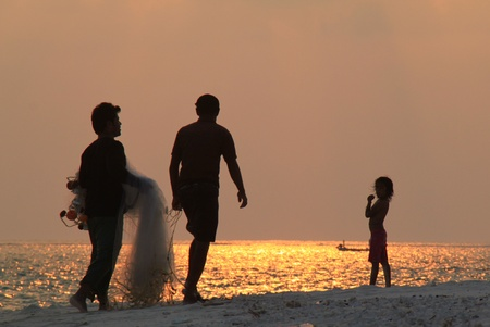 Young boy and fishermen on the beach in Agatti island