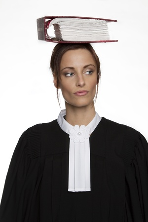 Women dress as a canadian attorney, balancing a red book of law on it on her head