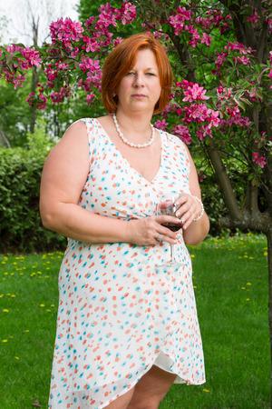 Foto für forty year old woman in summer dress, having a glass of wine under a cherry tree - Lizenzfreies Bild