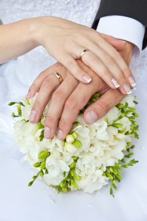 Foto de Hands with wedding rings and a wedding bouquet - Imagen libre de derechos