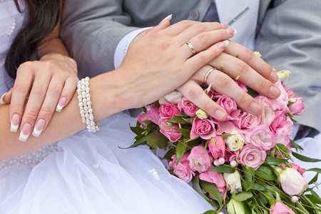 Hands of a newly-married couple with rings on a wedding bouquet